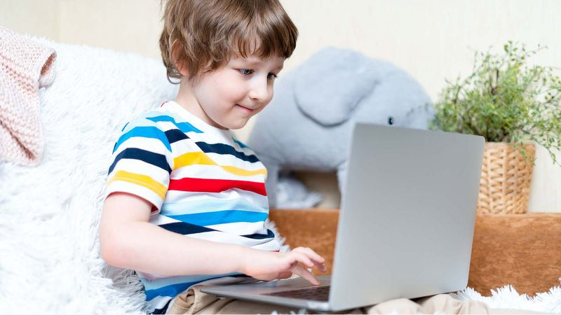 A young child enjoys the newly-available Jamf Teacher benefits of Remote Class, Raise Hand, and messaging on his Mac laptop.