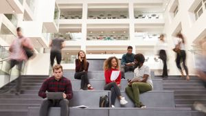 Students at higher education institution learning in study hall.