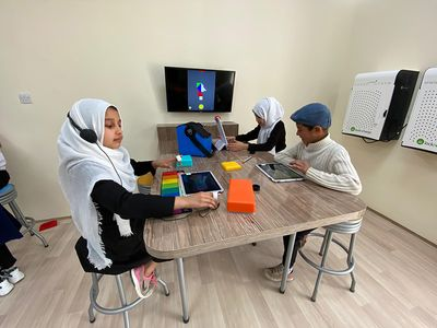 MATTER Innovation Hub students at work in Afghanistan. A girl in a black dress, sneakers, and a white headscarf crowned by headphones works with Sphero Specdrums and a Musical Play Pad. Across a table another girl in a black dress and white headscarf