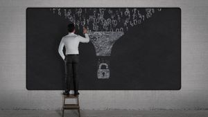 Man draws on chalkboard. Binary data filtering into a security lock.