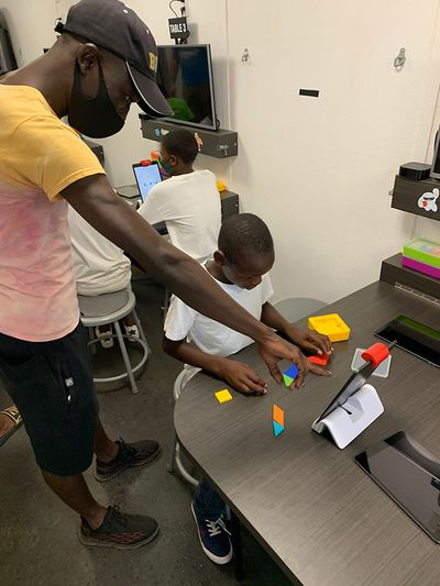 Three students and a teacher at a Zimbabwe MATTER Innovation Hub hard at work. The teacher points at an iPad propped up in front of a student in a white T-shirt, whose gaze is focused intently at colorful shaped he is putting together. Two other students