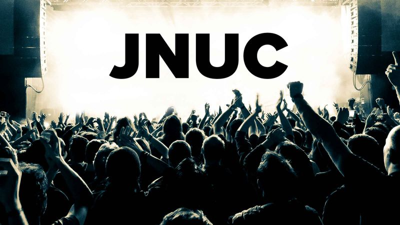 A crowd cheers in front of a JNUC sign