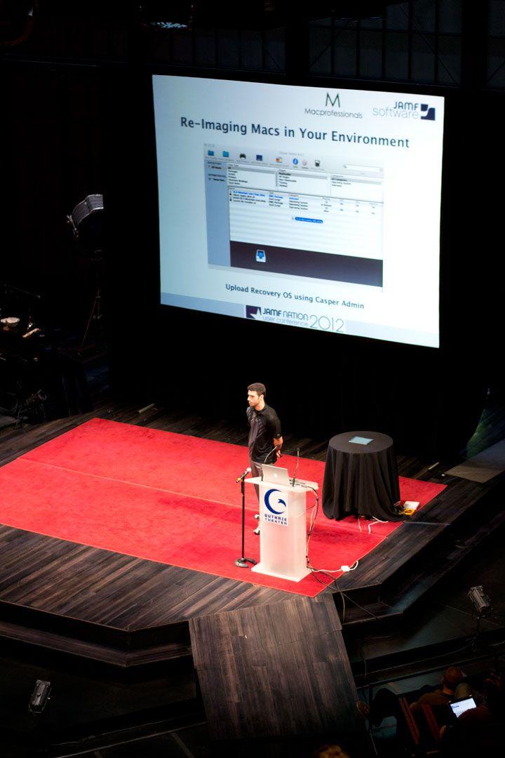 Matt Schalk stands at a JNUC podium to explain how to upgrade to OS Mountain Lion using Jamf Pro.