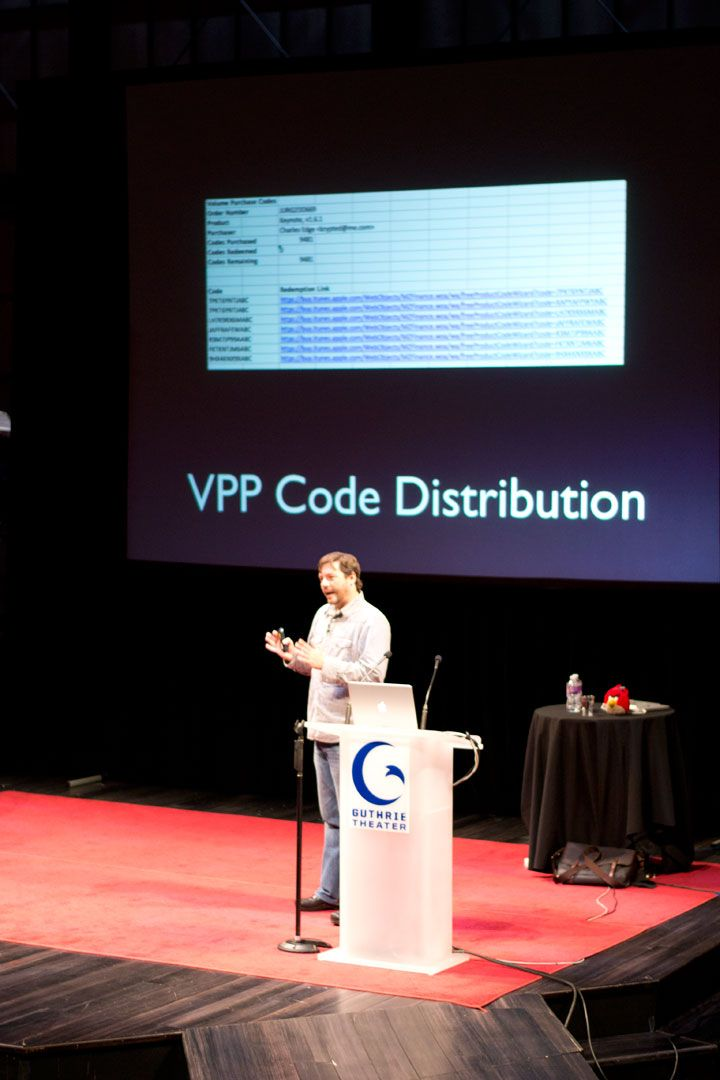 Jamf's Charles Edge stands at a podium and discusses VPP code distribution and large deployments at JNUC.