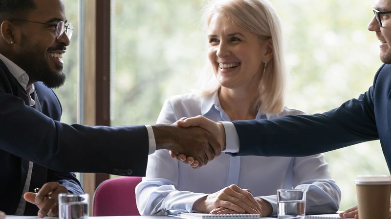 An employee shakes hands with someone on his first day onboarding to a new job.
