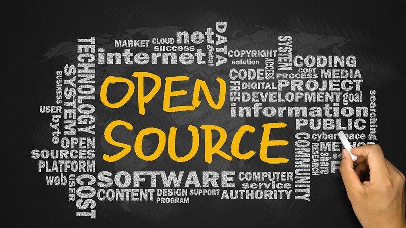 Hand on a chalkboard writes: Open Source.