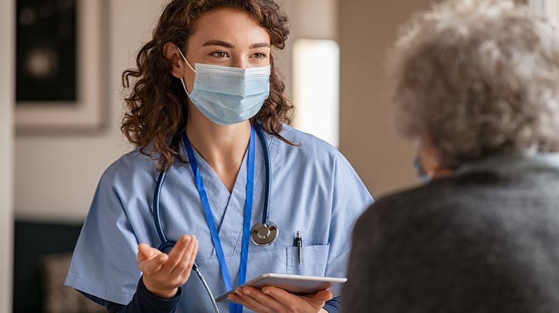 A nurse takes information from a patient using an iPad managed by Jamf Pro.