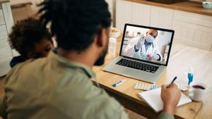 A father with a sick child on his shoulder uses Apple telehealth to speak with his doctor on a laptop.