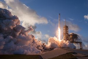 Space shuttle lifting off launchpad.