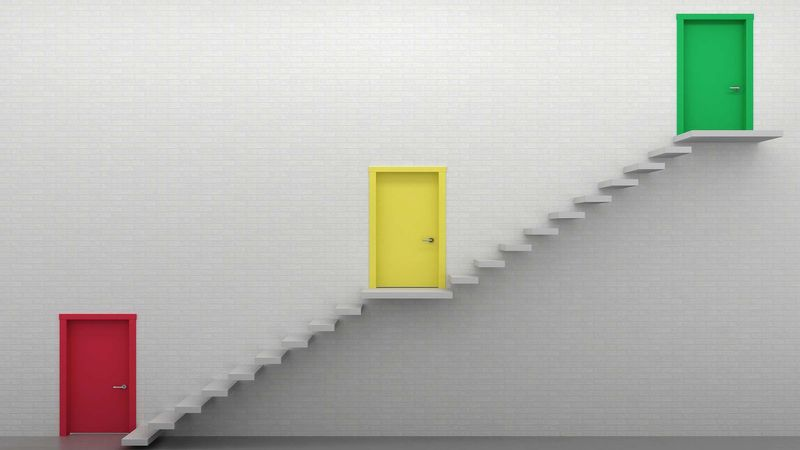 A red, yellow and green door on stairways symbolizing the three ways to enroll iOS devices into management.