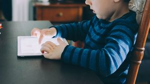 child sits at desk interacting with iPad
