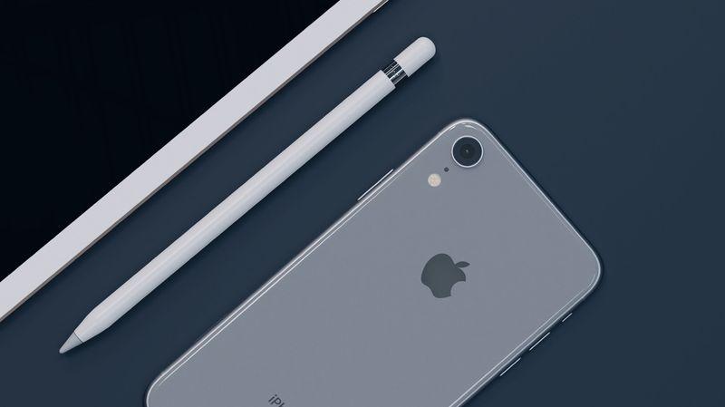 Apple iPhone, iPad, Pencil arranged on a desk.