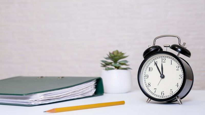 Notebook, pencil and alarm clock on a desk.